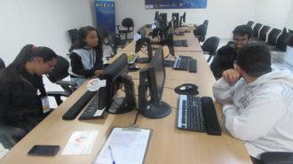 Foto de quatro usuários sentados em frente aos computadores.