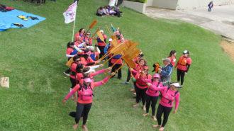 Foto das remadoras levantando o remo e formando um corredor.