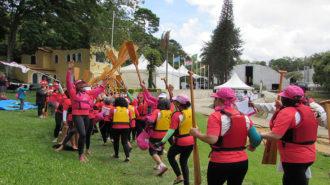Foto de competidoras passando pelo corredor de remadoras rosas.