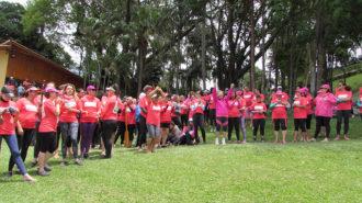 Foto de um grupo de remadoras rosas comemorando.