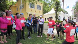 Foto de um grupo de remadoras, em pé, uma delas fala ao microfone.