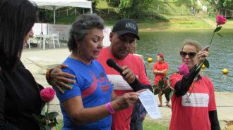 Foto de uma das remadoras falando ao microfone e sendo abraçada por um dos organizadores do evento.