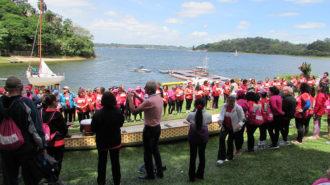 Foto da cerimônia das rosas. Remadoras Rosas reunidas ao redor de um barco Dragon Boat, segurando rosas.