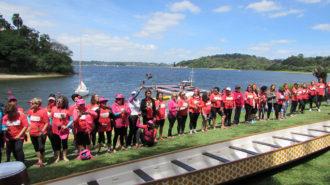 Foto das remadoras em frente ao barco Dragon Boat, ambas seguram uma rosa.