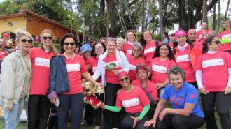 Foto da Dra. Linamara Rizzo Battistella (Secretária de Estado dos Direitos da Pessoa com Deficiência de São Paulo) com um grupo de remadoras sorrindo.