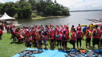 Foto de um grupo de remadoras sorrindo e acenando, em frente à Represa Guarapiranga.