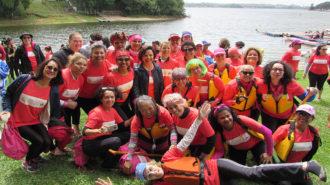 Foto da Dra. Linamara Rizzo Battistella (Secretária de Estado dos Direitos da Pessoa com Deficiência de São Paulo) com um grupo de remadoras sorrindo e acenando.