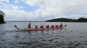 Foto de um grupo de remadoras no barco Dragon Boat na Represa Guarapiranga.