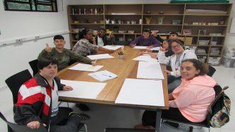 Foto da sala de artes. Nove usuários sentados próximos à mesa, desenhando em folhas brancas.
