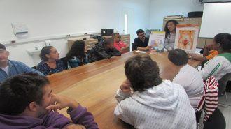 Foto da sala de artes. 10 usuários e dois técnicos sentados próximos à mesa. Os técnicos seguram cartazes com imagens do corpo humano.