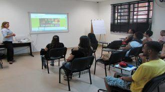 Foto da sala de aula. Em primeiro plano, 10 usuários sentados em cadeiras pretas. Ao fundo, uma técnica em pé.