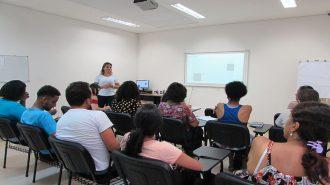 Foto da sala de aula. 11 usuários sentados em cadeiras pretas e uma técnica em pé.