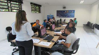 Foto da sala de aula. 9 usuários sentados em frente aos computares e uma técnica em pé na sala de aula.