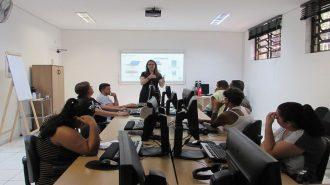 Foto da sala de aula. Em primeiro plano, 7 usuários sentados em frente aos computadores. Ao fundo, uma técnica e a lousa interativa.