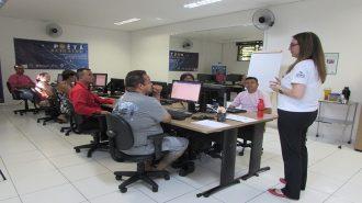 Foto da sala de aula. 7 usuários sentados em frente aos computadores e uma técnica em pé.