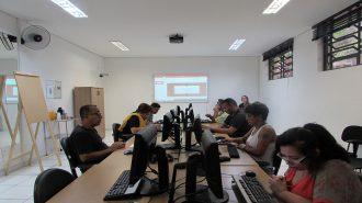 Foto da sala de aula. Em primeiro plano, 7 usuários sentados em frente aos computadores. Ao fundo uma técnica sentada em frente ao computado próximo à lousa interativa.