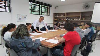 Foto da sala de artes. Nove usuários sentados próximos à mesa e uma técnica em pé. Ambos fazem dobradura com uma folha de papel branca.