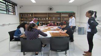 Foto da sala de artes. Oito usuários próximos à mesa, desenhando em folhas brancas. Duas técnicas em pé, acompanham a atividade.