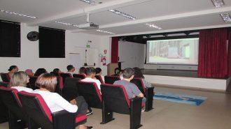 Foto do anfiteatro. Em primeiro plano, 11 usuários e duas técnicas sentados em cadeiras pretas e vermelhas. Ao fundo, o telão do auditório.