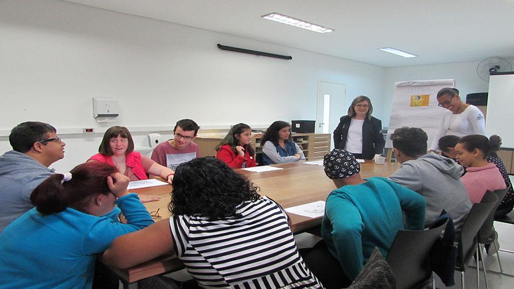 Foto da sala de artes. Em primeiro plano, 11 usuários sentados próximos à mesa e duas técnicas em pé.