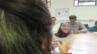Foto de uma usuária segurando um espelho e sorrindo.