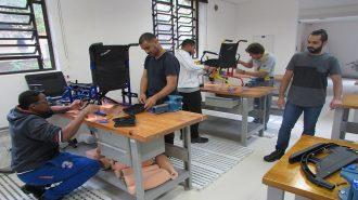 Foto da oficina. Quatro usuários mexendo com cadeiras de rodas e um professor observando.