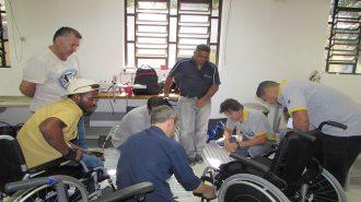 Foto da oficina. Um professor mexendo em uma cadeira de rodas e sete usuários observando.