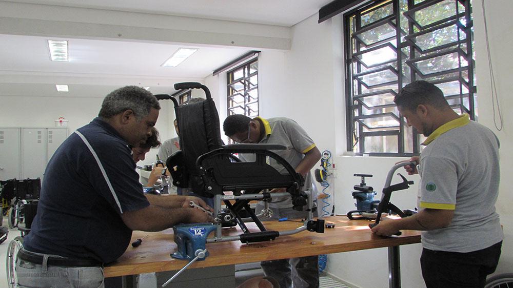 Foto da oficina. Quatro usuários mexendo nas peças de uma cadeira de rodas.