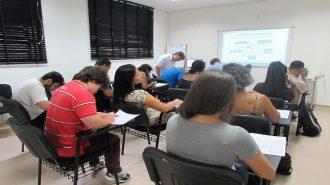 Foto da sala de aula. 12 usuários sentados em cadeiras pretas e um técnico em pé.