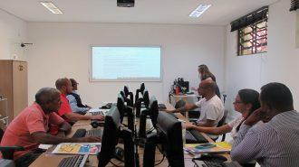 Foto do laboratório. Em primeiro plano, seis usuários sentados em frente aos computadores. Ao fundo, uma técnica olhando para o computador.