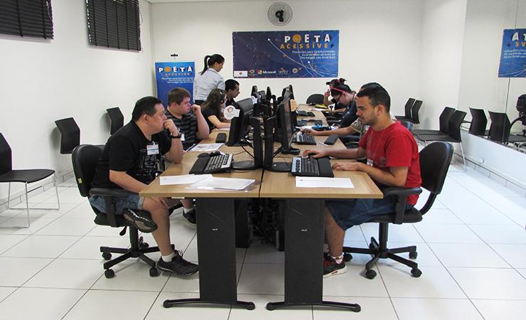 Usuários sentados em frente aos computadores no curso de alfabetização digital