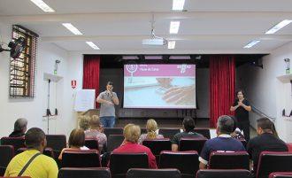 Em primeiro plano, usuários sentados em poltronas no auditório. Ao fundo, um palestrante e um intérprete.