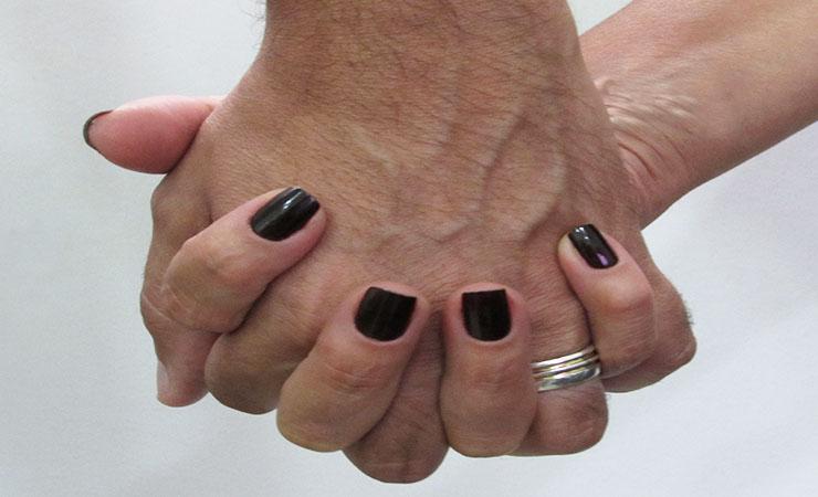 Foto de uma mão feminina e uma masculina entrelaçadas