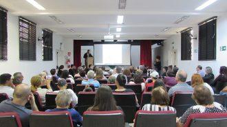 Imagem: Em primeiro plano, pessoas sentadas em poltronas. Ao fundo, o palco do auditório, o palestrante e um telão.
