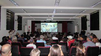 Imagem: Em primeiro plano, pessoas sentadas em poltronas. Ao fundo, o palco do auditório e uma tela com a imagem de usuários em uma das aulas.