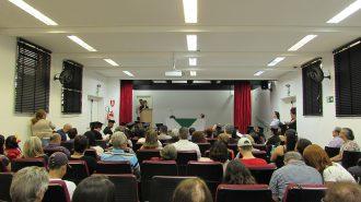 Imagem: Em primeiro plano, pessoas sentadas em poltronas. Ao fundo, o palco do auditório, a palestrante e uma mesa.