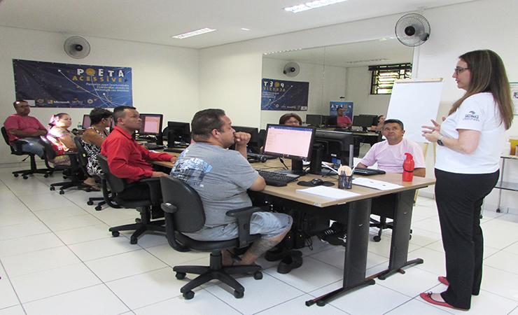 Usuários sentados em frente aos computadores e uma técnica em pé