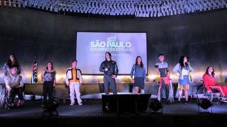 Foto de modelos com e sem deficiência no palco do auditório da Secretaria de Estado dos Direitos da Pessoa com Deficiência de São Paulo.