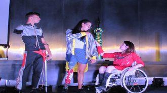 Foto da Izabelle Palma (Gestora do Programa Moda Inclusiva) e de modelos com deficiência no palco do auditório da Secretaria de Estado dos Direitos da Pessoa com Deficiência de São Paulo.