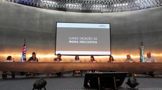Foto da Célia Leão (Secretária de Estado dos Direitos da Pessoa com Deficiência de São Paulo) e dos convidados no palco do auditório da Secretaria.