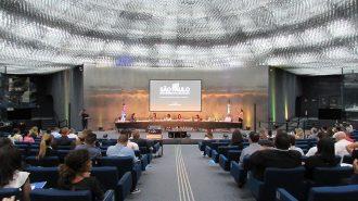 Foto do auditório. Em primeiro plano, pessoas sentadas em poltronas. Ao fundo, a Célia Leão (Secretária de Estado dos Direitos da Pessoa com Deficiência de São Paulo) e outros convidados.