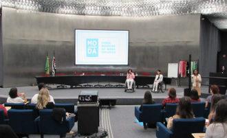 Em primeiro plano, usuários sentados em poltronas. Ao fundo, a Secretária de Estado, Célia Leão, e a Gestora do Programa Moda Inclusiva, Izabelle Palma, no palco do auditório da Secretaria de Estado dos Direitos da Pessoa com Deficiência.