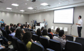Foto do auditório da HPE Brasil. Em primeiro plano, pessoas sentadas em poltronas. Ao fundo, Marcelo Scarabeli no palco.