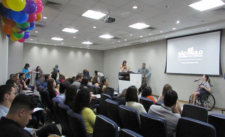 Em primeiro plano, pessoas sentadas em poltronas. Ao fundo, Izabelle Palma, gestora do Programa Moda Inclusiva, no palco do auditório da HPE Brasil.