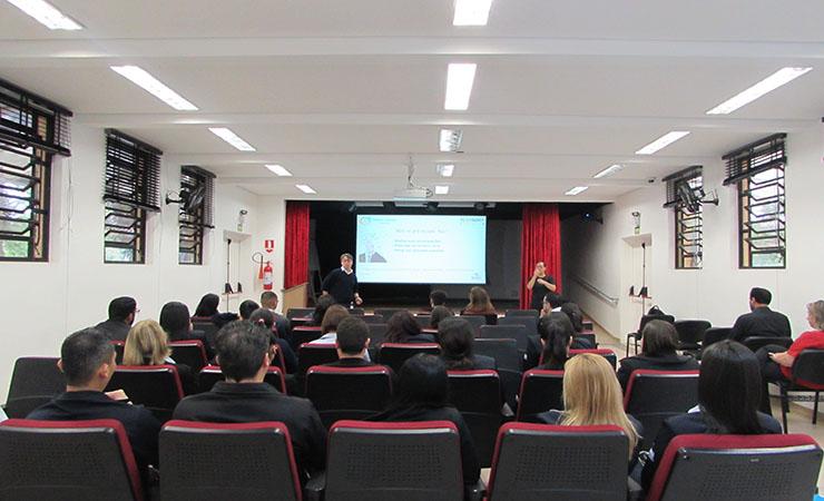Foto do auditório do Centro de Tecnologia e Inovação. Em primeiro plano, pessoas sentadas nas poltronas. Ao fundo, um palestrante e um intérprete de Libras.