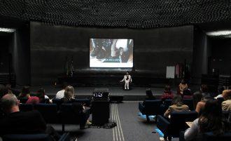 Foto do auditório da Secretaria. Em primeiro plano, pessoas sentadas em poltronas. Ao fundo, a gestora do Programa Moda Inclusiva no palco do auditório.