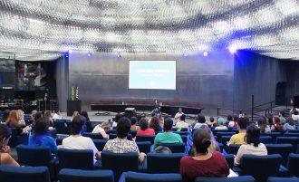 Foto do Auditório da Secretaria. Em primeiro plano, pessoas sentadas em poltronas. Ao fundo, a gestora do curso de Moda Inclusiva, Izabelle Palma