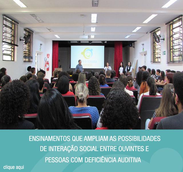Imagem do anfiteatro do Centro de Tecnologia e Inovação. Em primeiro plano, alunos sentados em poltronas. Ao fundo, o coordenador do curso de Libras da Secretaria de Estado dos Direitos da Pessoa com Deficiência de São Paulo, Luiz Oberdan, e a Gerente Administrativa do Centro de Tecnologia e Inovação, Luciana Fugimoto. Ao lado da imagem tem o texto ensinamentos que ampliam as possibilidades de interação social entre ouvintes e pessoas com deficiência auditiva.