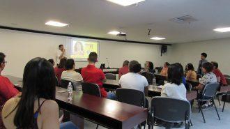 Imagem da sala de aula. Alunos sentados em cadeiras, próximos de uma mesa formato ferradura. Ao fundo, o professor fazendo sinais de Libras, ao lado da lousa interativa.