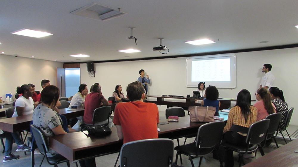Imagem da sala de aula. Alunos sentados em cadeiras, próximos de uma mesa formato ferradura. Ao fundo, a Secretária Célia Leão, o professor de Libras e a intérprete.